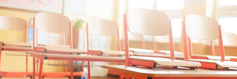 Pusta sala lekcyjna z szkolnymi biurkami, krzesłami i blackboard, jest edukacja starego odizolowane pojęcia obraz stock