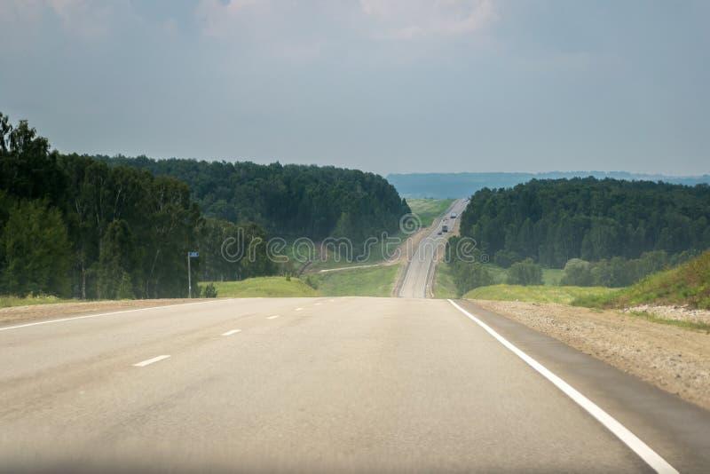 Pusta sekcja wsi autostrada Z Odległym ruchem drogowym samochody, ciężarówki Przed lato burzą fotografia stock