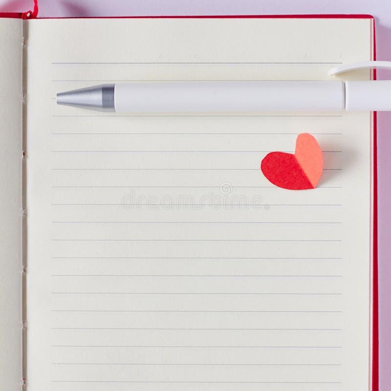 Pusta strona w notatniku, piórze i czerwieni papierowym sercu, obraz stock