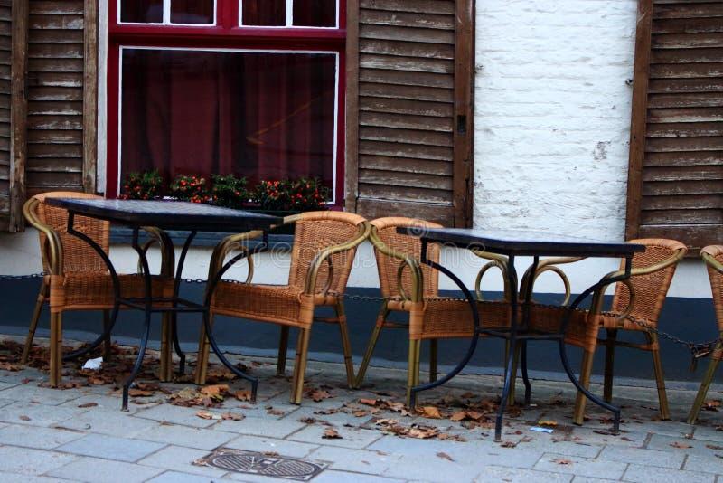 Pusta uliczna kawiarnia w europejskim starym miasteczku Opróżnia stoły, krzesła przeciw staremu białemu ceglanemu domowi z i zdjęcia stock