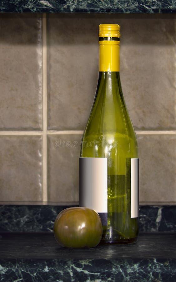 Pusta wino butelka i jeden pomidory fotografia stock