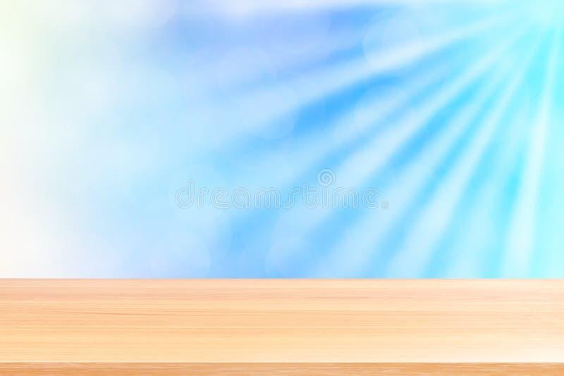 Puste drewno stołu podłoga na miękkim błękitnym bokeh świateł promieniu błyszczą gradientowego tło, drewniana deska pusta na błęk obrazy stock