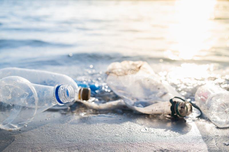 Puste klingeryt butelki na plaży, seashore i skażenie wody pojęciu, zdjęcie royalty free