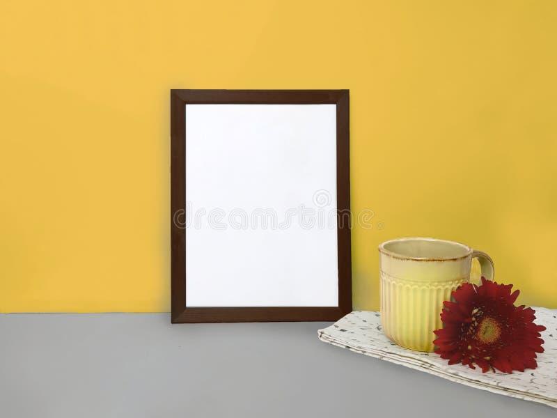 Puste miejsce rama dla projekta, ceramiczna filiżanka z czerwonym kwiatem, pielucha na popielatym stole nad kolor żółty ścianą obraz royalty free