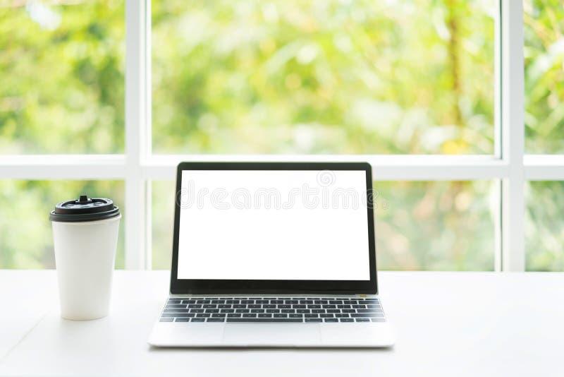 Pustego ekranu filiżanka na stole przy kawową kawiarnią z naturą w tle i laptop Technologia, biznesowy i nowożytny obraz stock