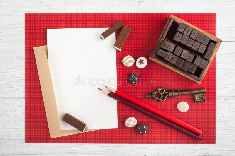 Pustego papieru notatka, rzemiosło koperta na czerwieni fotografia stock