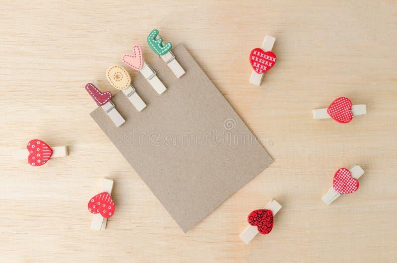 Pustego papieru notatka z miłość klamerkami i czerwonymi sercami na drewnianym backgr zdjęcia royalty free