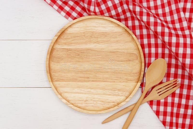 Pustego round drewniany talerz z łyżką, rozwidleniem i czerwieni gingham tablecloth na białym drewnianym stole, fotografia royalty free
