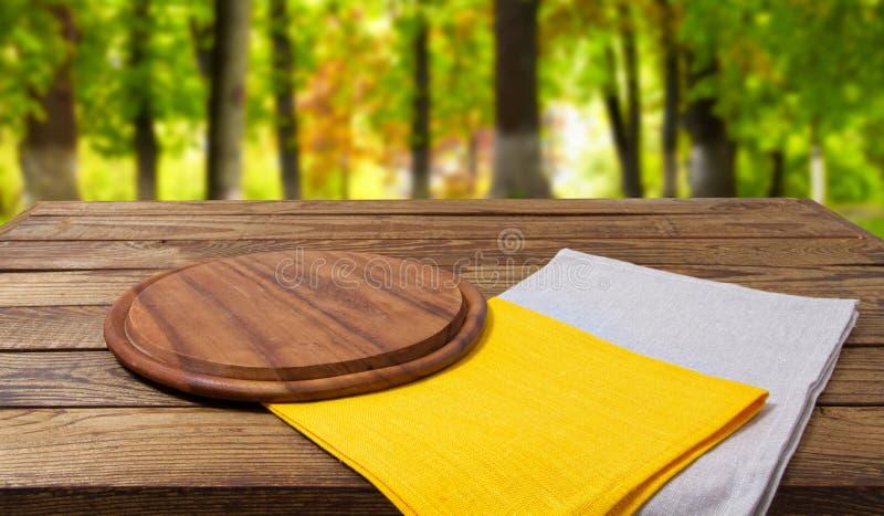Pustego tnącego biurko koloru żółtego popielate pieluchy na drewnianym stole na zamazanym parkowym tle zdjęcia stock
