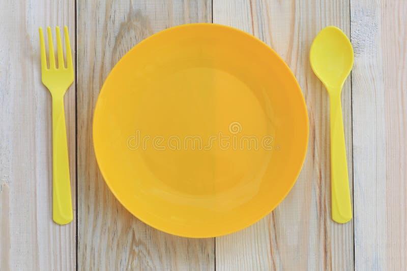 Pusty żółty plastikowy naczynie i łyżka umieszczający na drewnianej podłoga zdjęcia royalty free