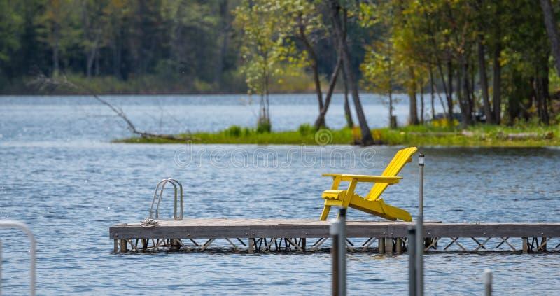 Pusty żółty pokładu krzesło na doku na jeziorze zdjęcia royalty free