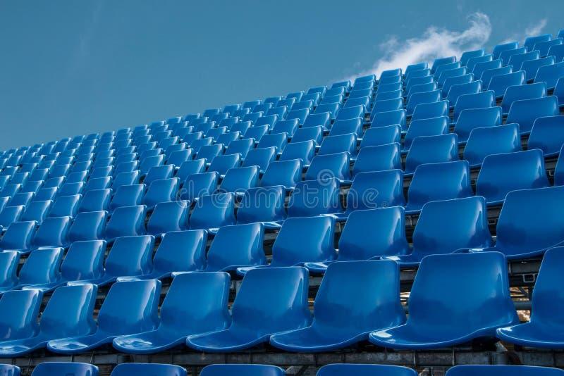 Pusty błękitny siedzenie w stadionie futbolowym z niebieskim niebem zdjęcie royalty free