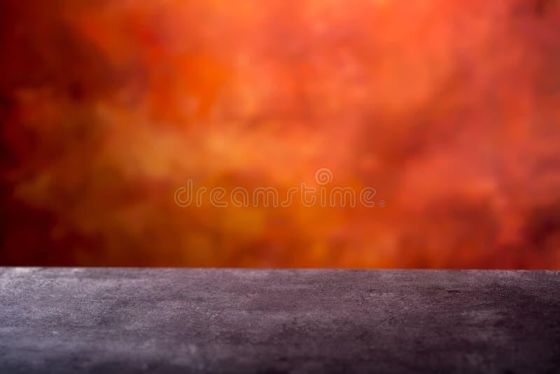 Pusty beton stołowy i abstrakcjonistyczny batikowy pomarańczowoczerwony tło przygotowywający dla photomontage Opróżnia przestrzeń zdjęcie stock