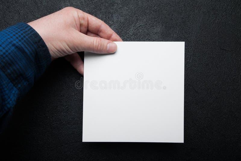 Pusty białego kwadrata prześcieradło papier w ręce na czarnym tle zdjęcie royalty free