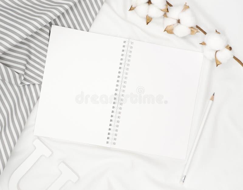 Pusty biały ślimakowaty notatnik z ołówkiem, bawełna kwiaty, siwieje lampas tkaninę i drewnianego list na białym łóżkowym prześci fotografia stock