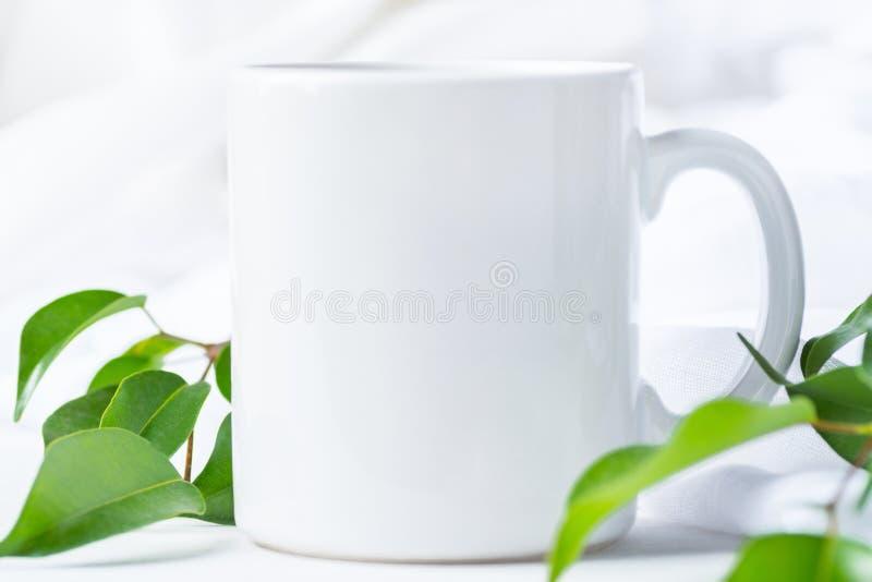 Pusty Biały kubka Mockup na Bawełnianym Bieliźnianym tkaniny tle Świeże gałąź z Zielonymi liśćmi Szablon przestrzeń dla grafiki zdjęcie royalty free