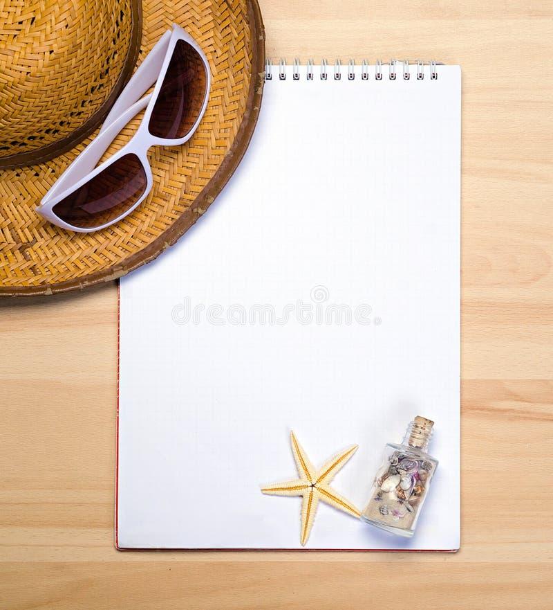 Pusty biały notatnik na drewnianej stół powierzchni z plażowym kapeluszem, morze zdjęcie stock