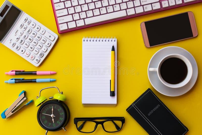 Pusty biały notepad z biurowymi i osobistymi akcesoriami odizolowywającymi na żółtym tle fotografia stock