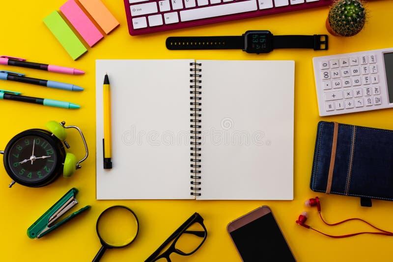 Pusty biały notepad z biurowymi i osobistymi akcesoriami odizolowywającymi na żółtym tle obraz stock