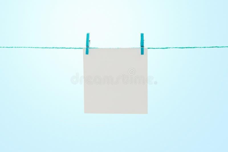 Pusty biały nutowy papierowy obwieszenie na arkanie przeciw pogodnemu niebieskiemu niebu z kopii przestrzenią obraz stock