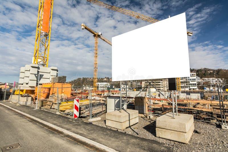 Pusty billboard przed żurawiami na wielkiej budowie zdjęcie stock