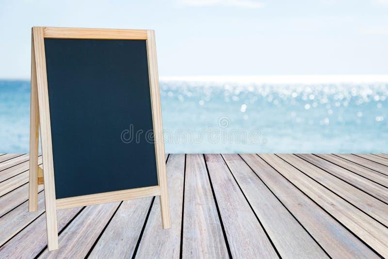 Pusty blackboard znak i drewniany taras z piaskiem wyrzucać na brzeg obrazy royalty free