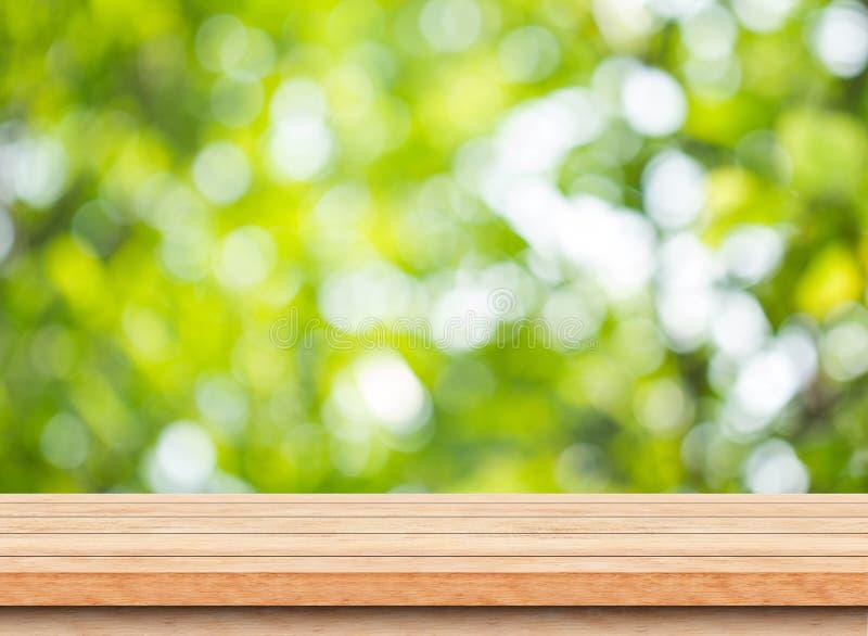 Pusty brown drewniany stołowy wierzchołek z plamy zieleni bokeh drzewnym tłem fotografia royalty free