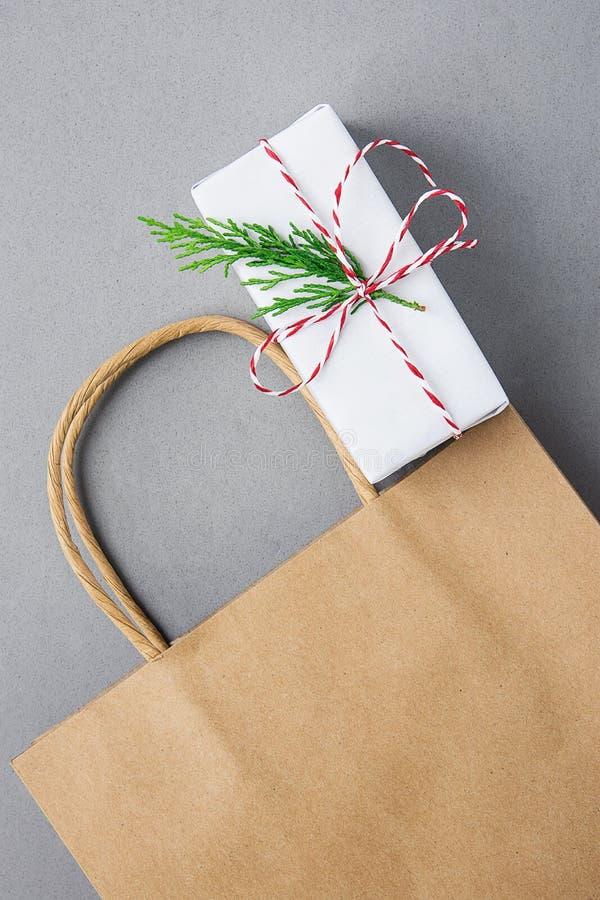 Pusty Brown rzemiosła Papierowej torby białych bożych narodzeń prezenta pudełko z Czerwonej faborek zieleni Jałowcową gałązką na  obrazy stock