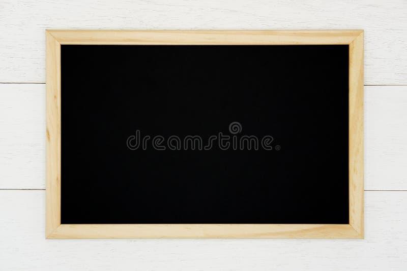 Pusty chalkboard na białym drewnianym deski tle zdjęcie royalty free