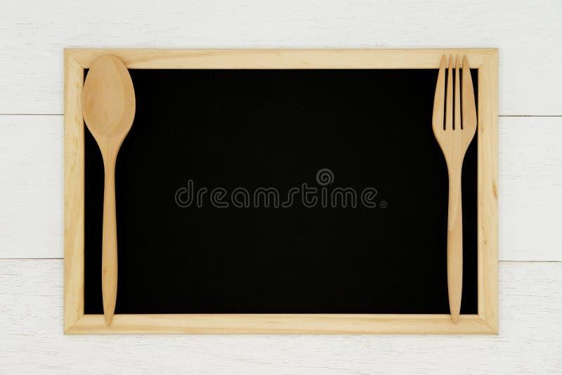 Pusty chalkboard z drewnianą łyżką i rozwidlenie na białym drewnianym deski tle zdjęcie royalty free