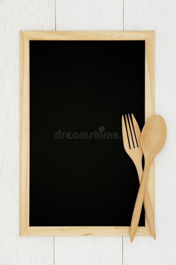 Pusty chalkboard z drewnianą łyżką i rozwidlenie na białym drewnianym deski tle fotografia stock