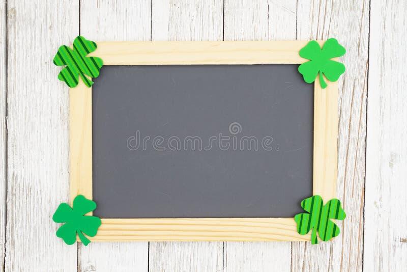 Pusty chalkboard z zielonymi shamrocks na wietrzejącym wybielaniu textured drewnianego tło obraz royalty free