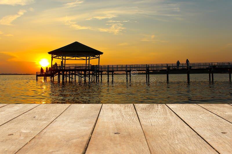 Pusty drewniany stół lub deska z pawilonem przy jeziorem lub rzeką z czasem na tle zmierzchu lub wieczór zdjęcia stock