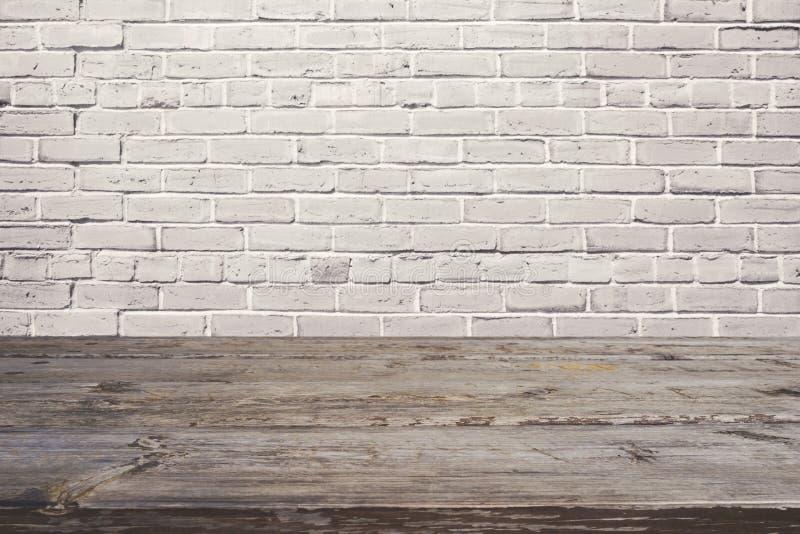 Pusty drewniany stół nad białym ściana z cegieł Tło dla produktu montażu obraz stock