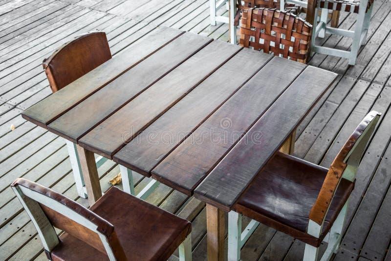 Pusty drewniany stół w restauracji z cztery pustymi krzesłami - vintag fotografia royalty free
