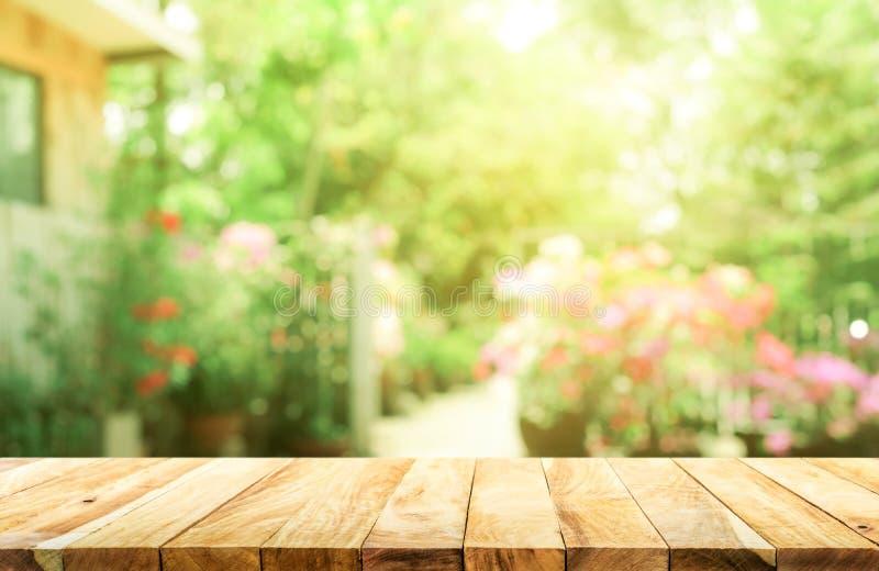 Pusty drewniany stołowy wierzchołek na plama abstrakta zieleni od ogródu fotografia stock