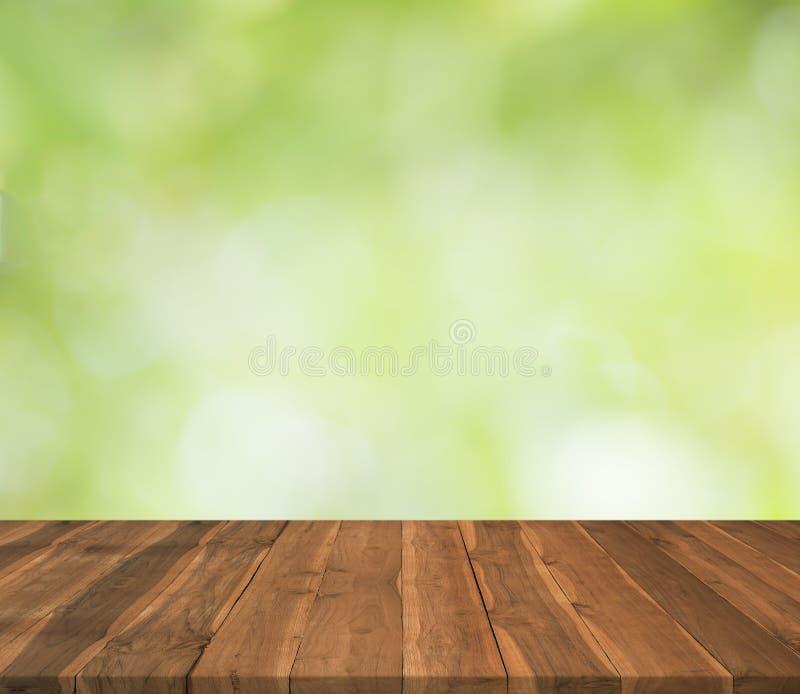 Pusty drewniany stołowy wierzchołek na zamazanym abstrakt zieleni tle zdjęcie royalty free