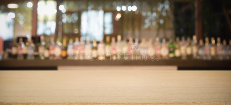 Pusty drewniany stołowy wierzchołek z Defocused tłem i butelki restauracji, baru lub bufeta tło, obrazy stock