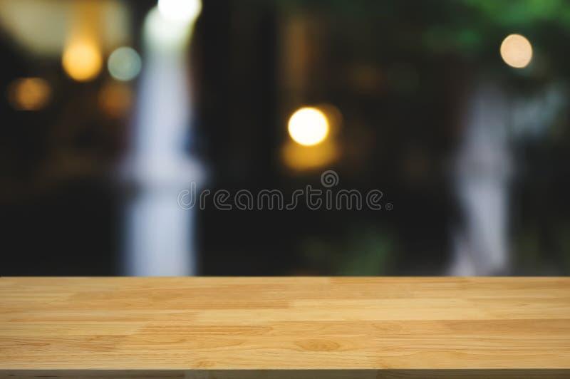 Pusty drewno stół z montażem zamazywał kawowego cukiernianego tło zdjęcie stock