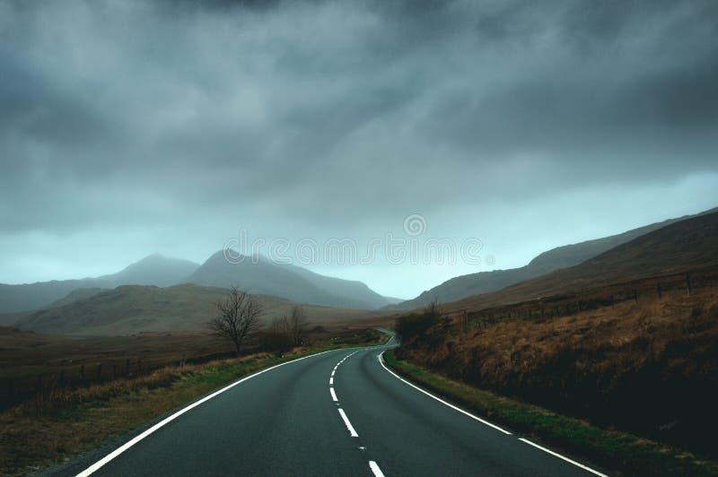 Pusty drogowy kłoszenie w kierunku gór Snowdonia na burzowym zima dniu fotografia stock