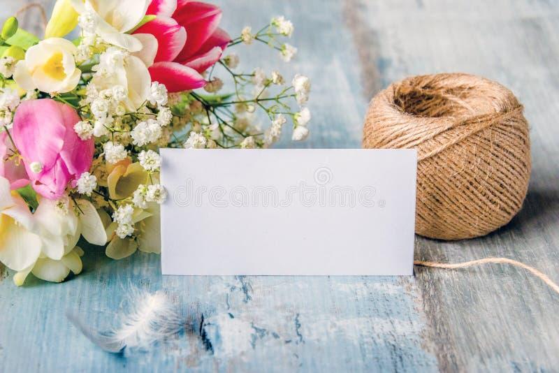 pusty karty powitanie Wiosny piórko nad błękitnym nieociosanym drewnianym tłem i kwiaty zdjęcie royalty free