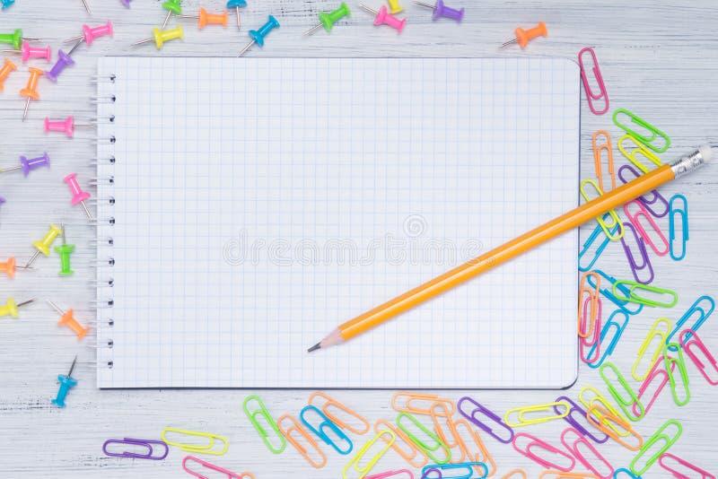 Pusty kawałek papieru w klatce na stole z ołówkiem otaczającym barwić klamerkami, zdjęcie stock