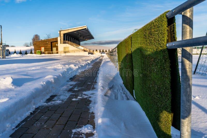 Pusty Kolorowy futbol &-x28; Soccer&-x29; Stadiów siedzenia w zimie Zakrywającej w śniegu - Pogodny zima dzień zdjęcie royalty free