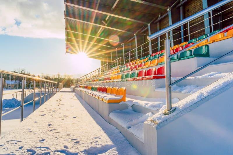 Pusty Kolorowy futbol &-x28; Soccer&-x29; Stadiów siedzenia w zimie Zakrywającej w śniegu - Pogodny zima dzień z słońce racą zdjęcia stock