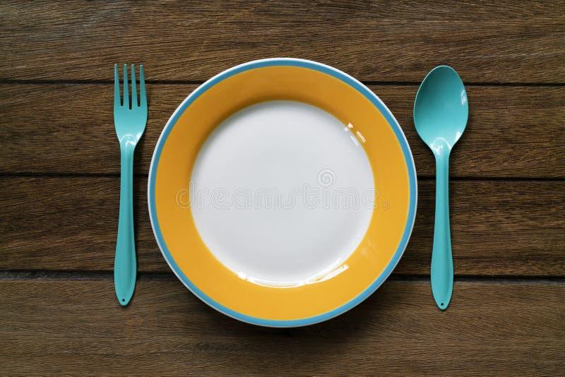 Pusty koloru talerz, rozwidlenie i łyżka na drewnianym stołowym tle, zdjęcie royalty free
