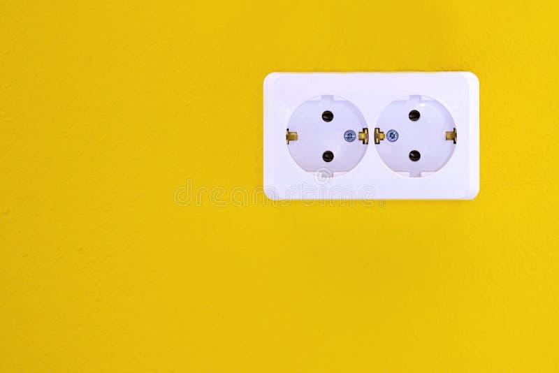 Pusty, niezatamowany europejski ścienny ujście zamknięty w górę żółtego tła na, Biała elektryczna nasadka na żółtej ścianie zbli? fotografia royalty free