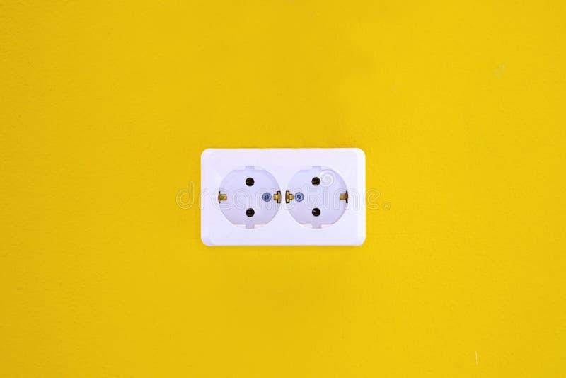 Pusty, niezatamowany europejski ścienny ujście zamknięty w górę żółtego tła na, Kolor żółty ściana z europejskim elektrycznym ujś zdjęcia royalty free