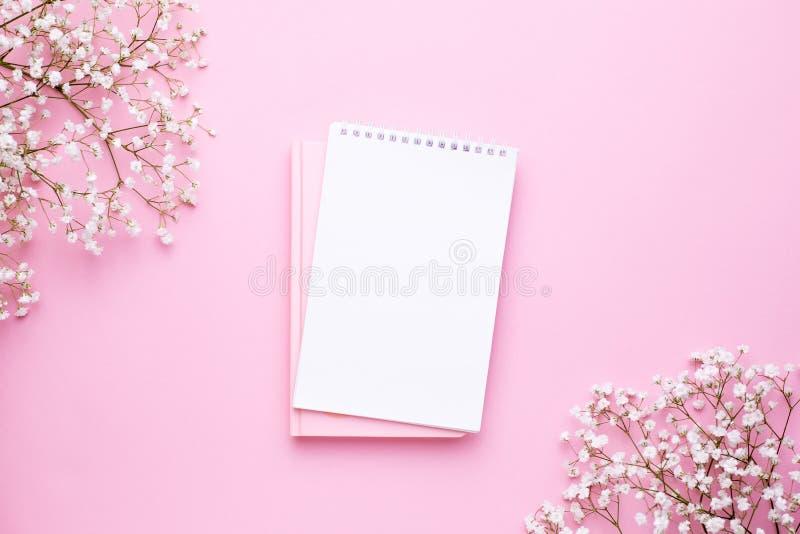 Pusty notatnik i biali kwiaty na r??owym pastelowym sto?owym odg?rnym widoku w mieszkaniu k?a?? styl Kobiety pracuj?cy biurko zdjęcia royalty free