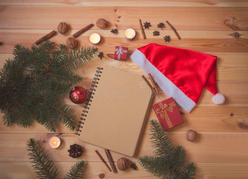 Pusty notatnik, jedlinowe gałąź, Santa kapelusz, boże narodzenia piłki, świeczki, pikantność i prezenty, zdjęcie stock