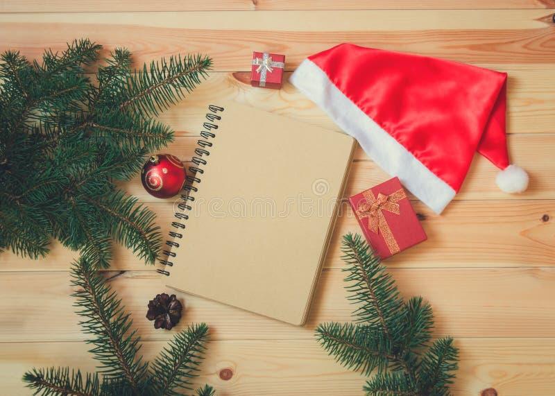 Pusty notatnik, jedlinowe gałąź, Santa kapelusz, boże narodzenia piłki i prezenty na drewnianym tle, obraz stock